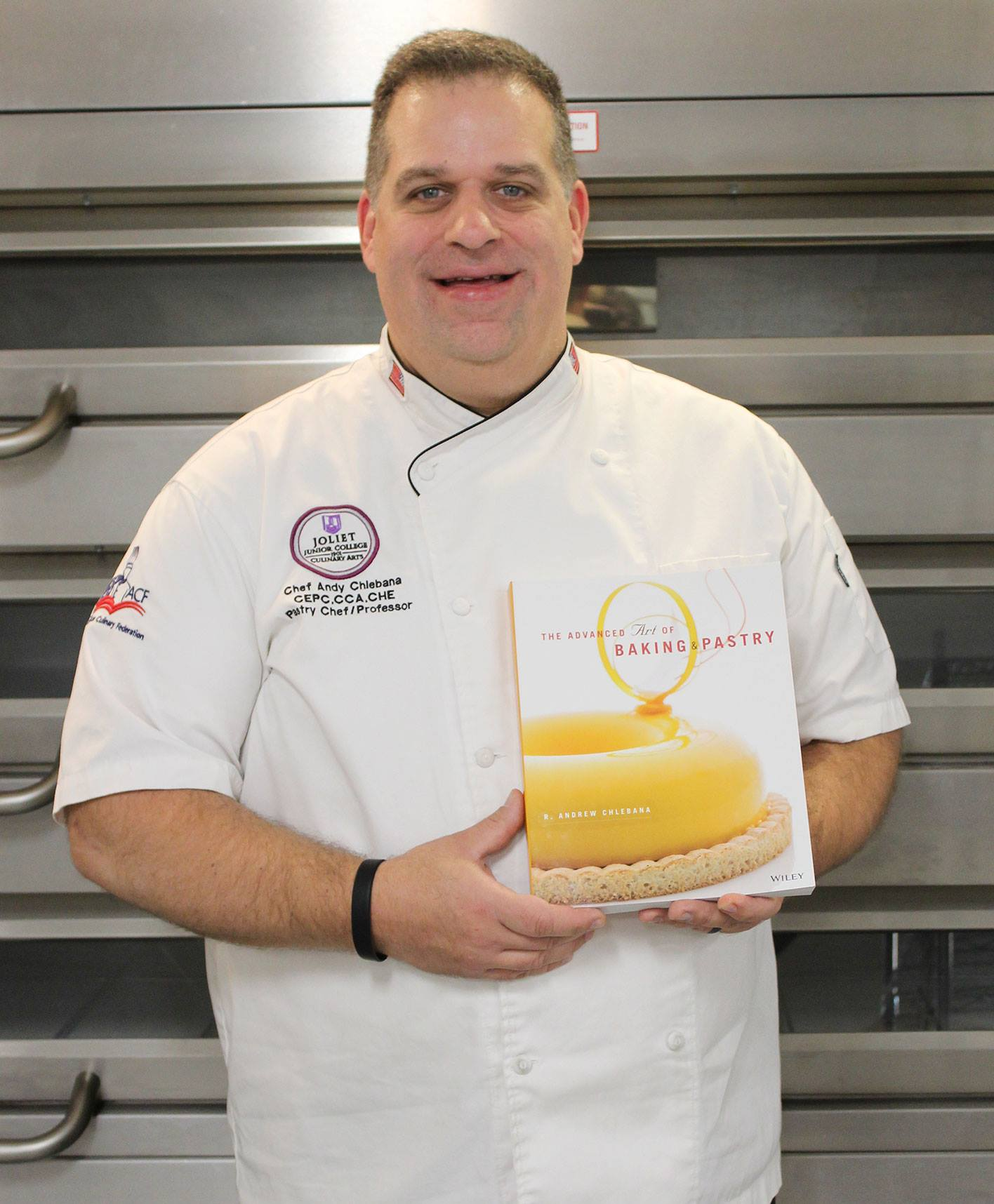 JJC professor of culinary arts, Andy Chlebana, holds a copy of his new textbook.