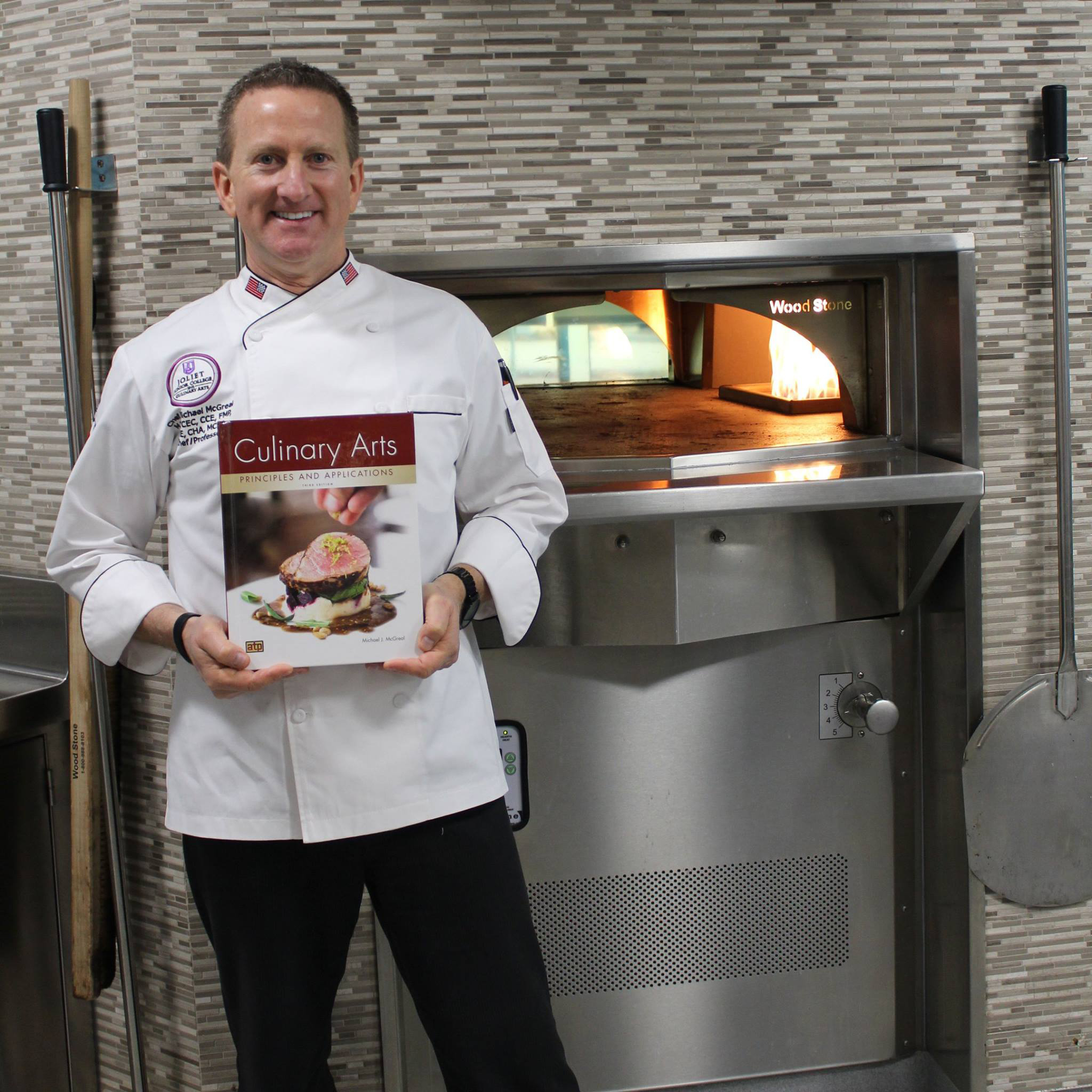 "Chef Mike McGreal holding a copy of his textbook, ""Culinary Arts Principles and Applications."""