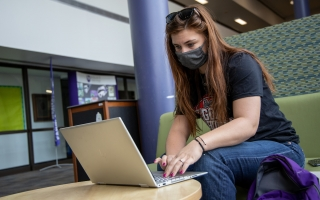 A student is on her laptop, applying for a Fall 2021 scholarship