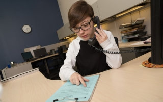 student on phone in office