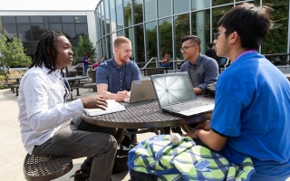 students on laptop outside